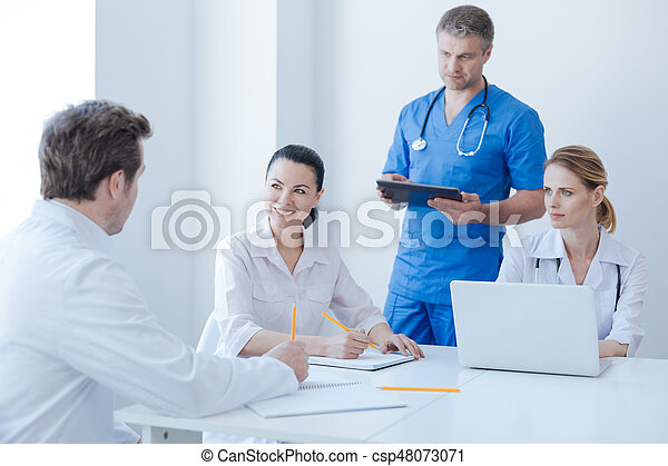 Energetic oncologists enjoying morning routine at the hospital - csp48073071