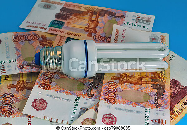 Energy saving light bulb close-up on a background of banknotes. - csp79088685