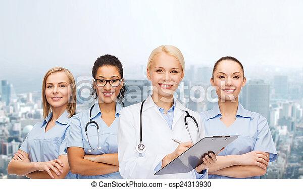 Médico sonriente y enfermeras con estetoscopio - csp24313930