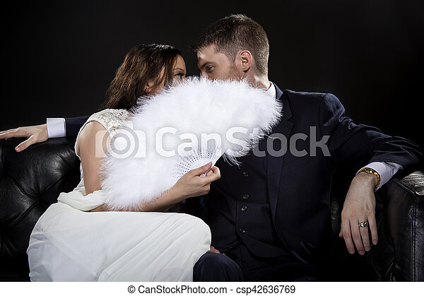 Engaged Couple Hiding Behind a Vintage Fan - csp42636769