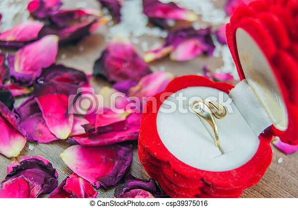 Engagement ring in a box, rose petals - csp39375016