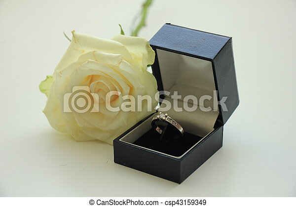 Classic solitaire engagement ring in box and white rose stock photo ...