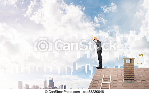 Engineer man standing on roof and looking down. Mixed media - csp58230046