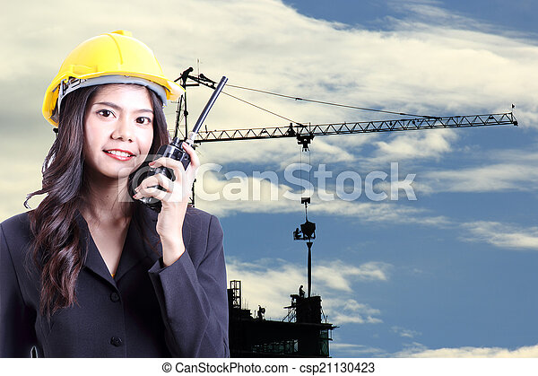 Engineer woman talking with a walkie talkie - csp21130423