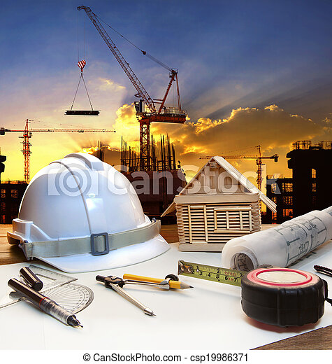 engineer working table plan, home model and writing tool equipment against building construction crane with evening dusky sky  - csp19986371