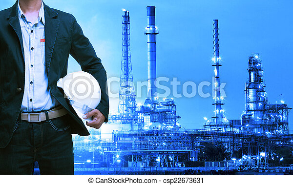 engineering man and safety helmet standing against oil refinery - csp22673631