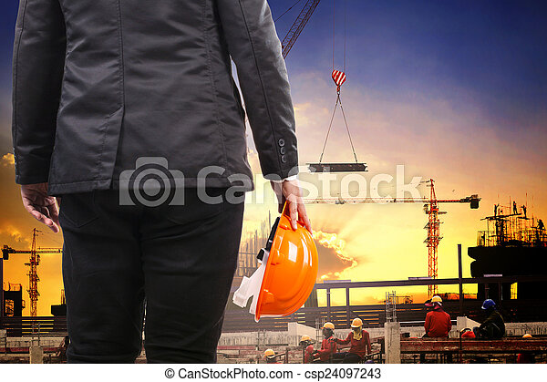 engineering man holding safety helmet and working in building co - csp24097243