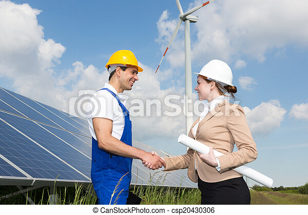 Engineers shake hands in front of solar panels and wind turbine - csp20430306