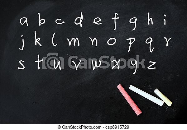 English alphabet handwritten with white chalk on a blackboard - csp8915729