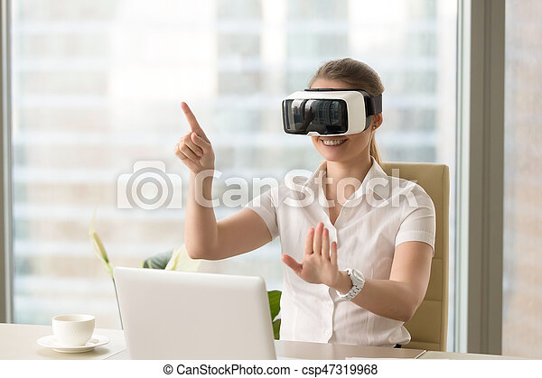 Enjoyed young woman using VR headset with gestures - csp47319968