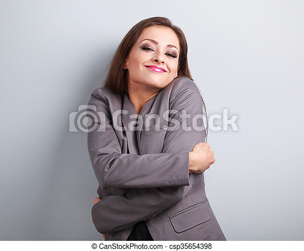 Enjoying business woman hugging herself with natural emotional face. Love concept of yourself.  - csp35654398