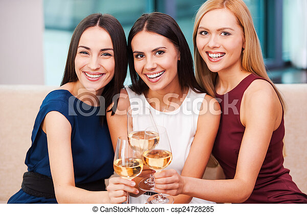 Enjoying great time together. Three beautiful young women in evening gown sitting on the couch and holding glasses with wine - csp24728285
