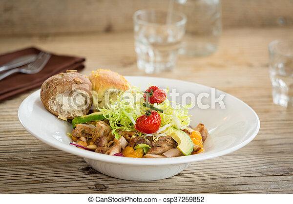 Ensalada de pollo servida con dos panecillos - csp37259852