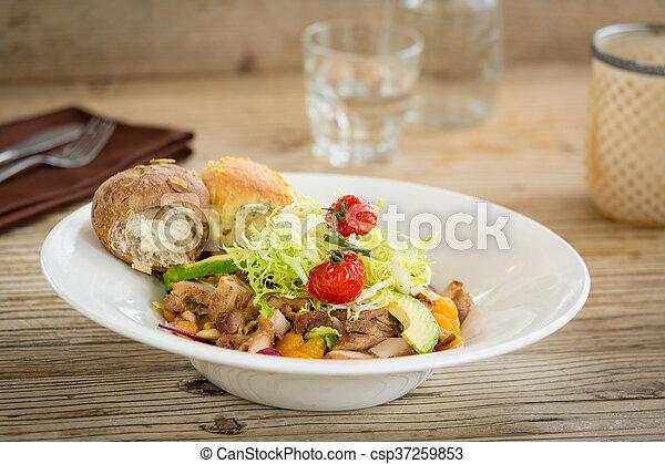 Ensalada de pollo servida con dos panecillos - csp37259853