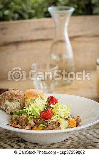 Ensalada de pollo servida con dos panecillos - csp37259862