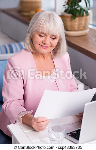 Enthusiastic senior lady studying the report - csp43393705