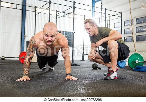 Entrenador ayudando al hombre a hacer flexiones - csp29072296