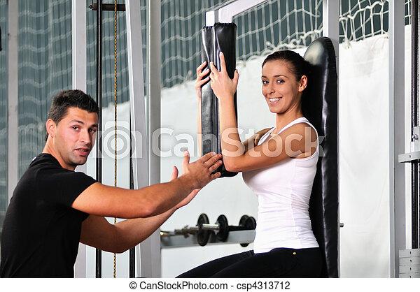 Una mujer en forma trabajando con entrenador personal - csp4313712