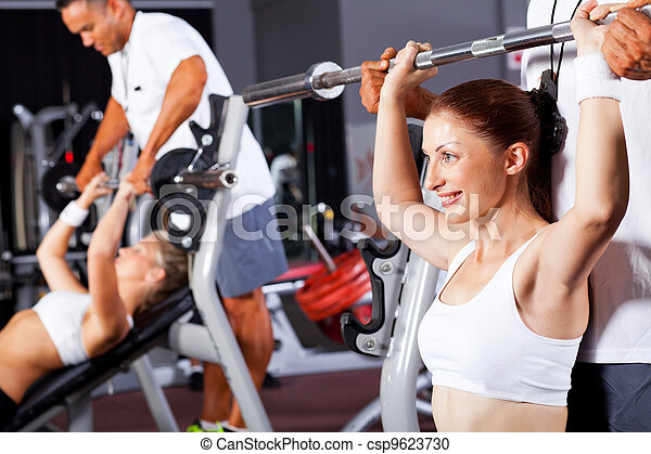 Mujer en forma con entrenador personal en gimnasia - csp9623730