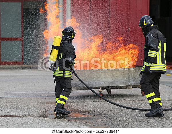 Bomberos con botellas de oxígeno fuera del fuego durante un ejercicio de entrenamiento - csp37739411