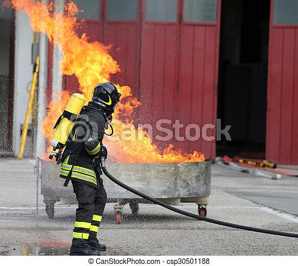 Bomberos con botellas de oxígeno fuera del fuego durante un ejercicio de entrenamiento - csp30501188