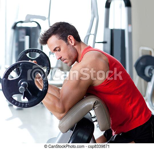 Hombre con equipo de entrenamiento de peso en el gimnasio deportivo - csp8339871