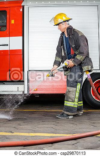 Bombero rociando agua en el suelo durante el entrenamiento - csp29870113