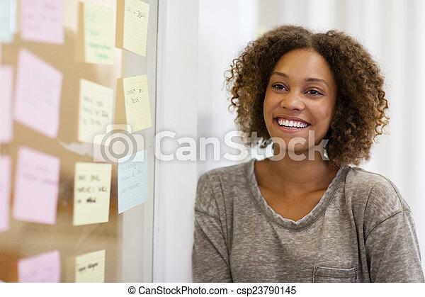 Entrepreneur smiling in front of her task cards - csp23790145