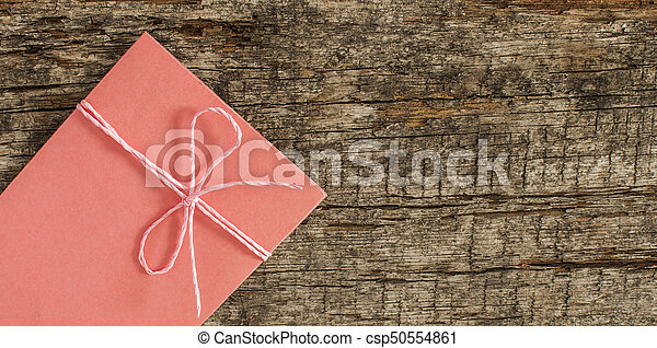 envelope tied with ribbon on wooden background - csp50554861