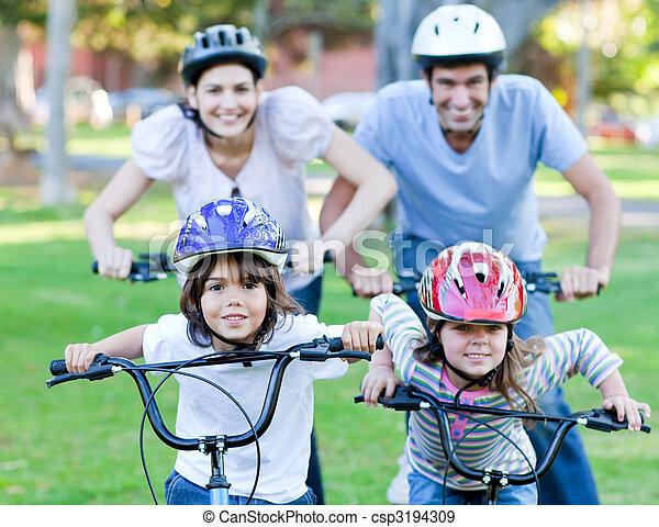 Familia feliz montando una bicicleta - csp3194309