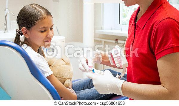 Näheres Bild des pädiatrischen Zahnarztes, der die Zahnhygiene auf Kiefermodell erklärt - csp56861653