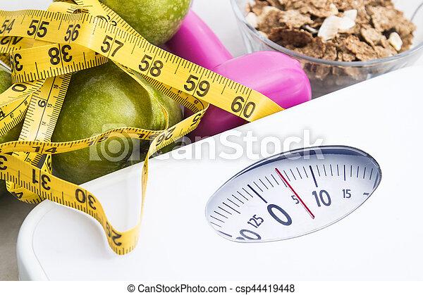 Escamas con cereales, fruta, peso y cinta miden y concepto de dieta y estilo de vida saludable - csp44419448