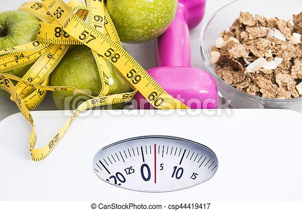 Escamas con cereales, fruta, peso y cinta miden y concepto de dieta y estilo de vida saludable - csp44419417