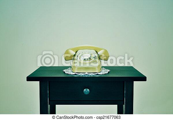 Un viejo teléfono rotatorio en una mesa, con un efecto retro - csp21677063