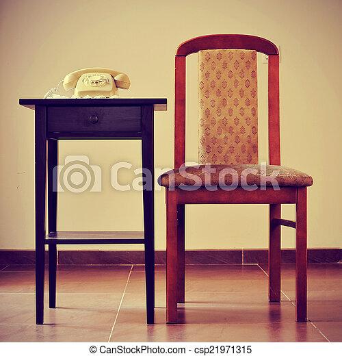Un viejo teléfono rotatorio en una mesa junto a una silla, con una ret - csp21971315