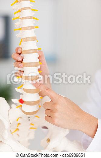 Un dedo apuntando al hueso de la columna - csp6989651