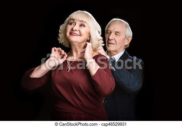 Un anciano sonriente poniendo collar a una esposa feliz en negro - csp46529931
