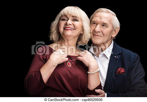Un anciano sonriente poniendo collar a una esposa feliz en negro - csp46529936