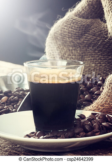 Espresso coffee in glass cup with coffee beans. - csp24642399