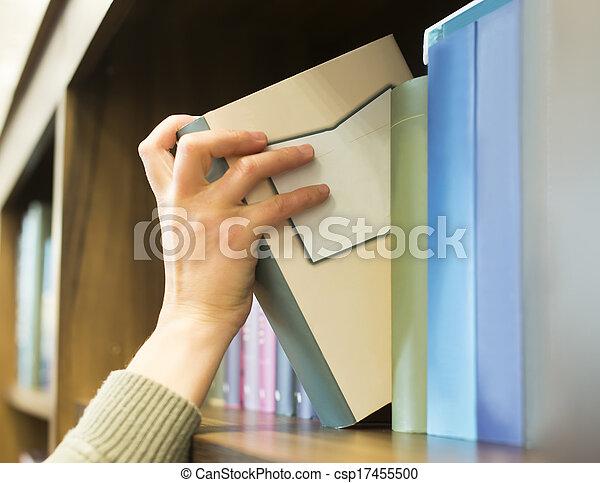 Mano sacando un libro de la estantería - csp17455500