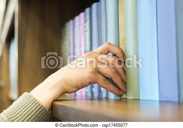 Mano sacando un libro de la estantería - csp17455077