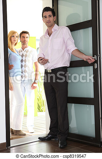 Estate agent showing couple around property - csp8319547