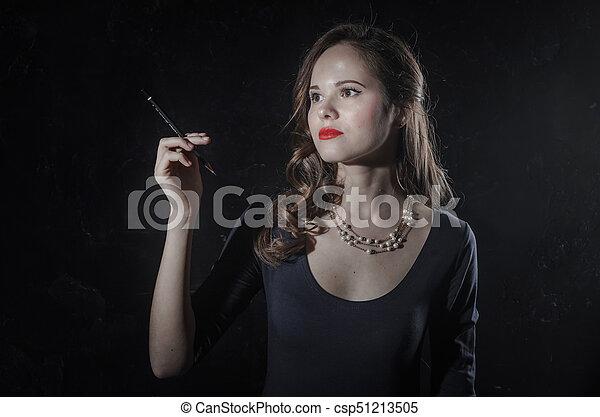 Una chica con un humor de ensueño. Estilo de cine negro mujer vestida con un bolígrafo negro en la mano. Foto de estudio. Una foto antigua - csp51213505