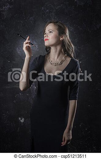 Una chica con un humor de ensueño. Estilo de cine negro mujer vestida con un bolígrafo negro en la mano. Foto de estudio. Una foto antigua - csp51213511