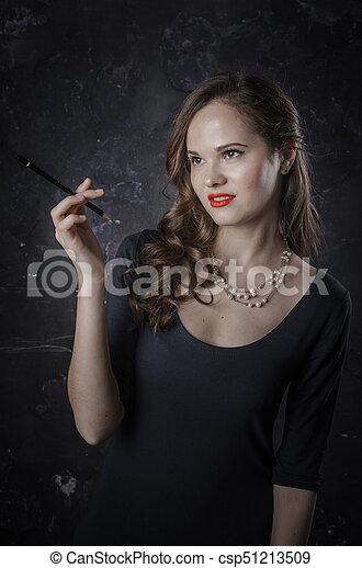 Mujer de mal humor y sonriente. Estilo de cine negro mujer vestida con pluma negra. Foto de estudio. Una foto antigua - csp51213509