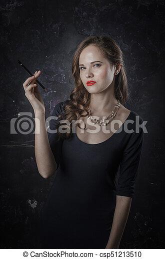 Mujer de mal humor despreciativamente mira a la cámara. Estilo de cine negro mujer vestida con pluma negra. Foto de estudio. Una foto antigua - csp51213510