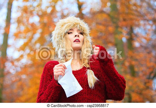 Mujer enferma estornudando en tejido al aire libre - csp23958817