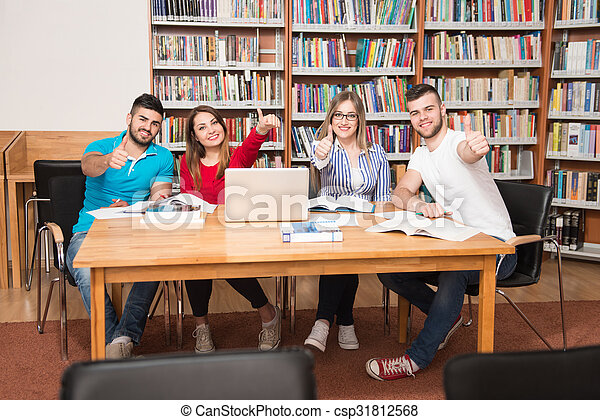 Estudiantes en una biblioteca mostrando pulgares arriba - csp31812568