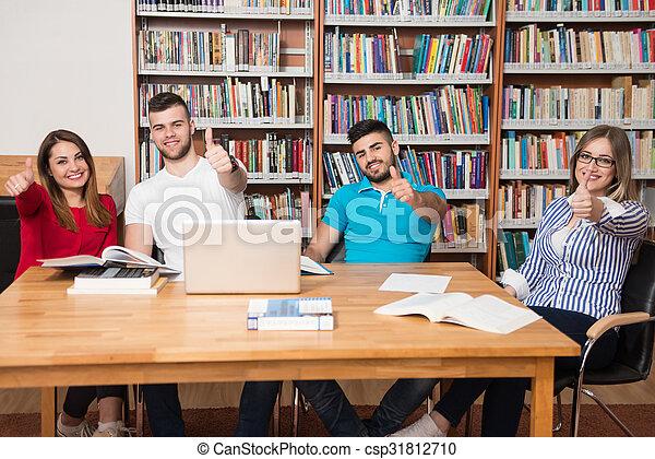 Estudiantes en una biblioteca mostrando pulgares arriba - csp31812710