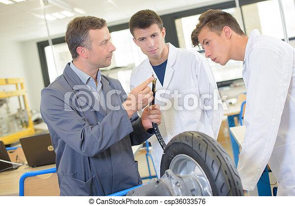 El profesor muestra a los estudiantes el adaptador para inflar neumáticos - csp36033576